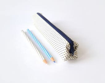 Small pencil case/zipper pouch in off-white with small navy dots, with a dark blue zip and a red and white chevron lining