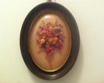Repurposed distressed frame with dried flowers under glads. Great for the victorian look!