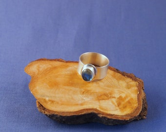 Sterling silver wide band ring with Swiss Blue Topaz cabochon.