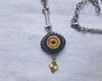 Pendant yellow white and black beads, bone, doll eye and small gold sequin embroidered