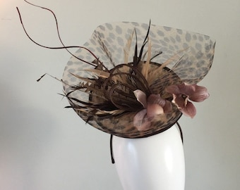 Leopard print sinamay with leopard print crin, sinamay loops, orchid fabric flowers and feathers along with curled quills