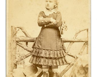Cabinet card of of well dressed young girl holding a hat and wearing striped stockings. Charles D. Fredricks photographer