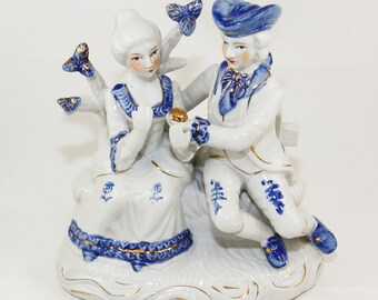 The Engagement Porcelain Figurine Colonial Couple sitting on a garden bench Blue and White glaze with Metallic Gold highlights