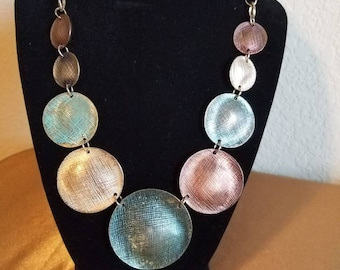 Multi colored metal necklace.  Jewel tones, torquoise, silver, copper disks.