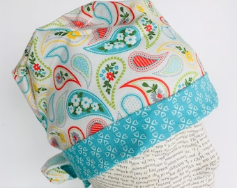 Tie Back Scrub Cap scrub hat with a white material with paisleys in teal yellow green and orange with a coordinating band 2t