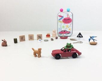 Cadeau de Noël pour les enfants. Jouets dans une petite boîte de voyage. Neufs & vintages petits trésors, animaux, clés, boutons, lettres, dés, pièces de jeu.