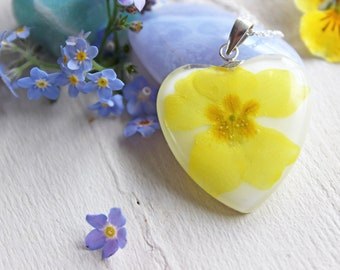 Heart pendant with white resin inlaid with a yellow Primrose flower