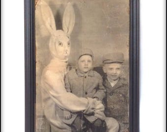 Aged reproduction unusual print of a creepy rabbit with two children - framed.
