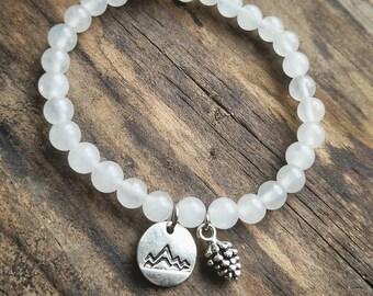White quartz gemstone beaded stretch bracelet with mountains and pinecone charm