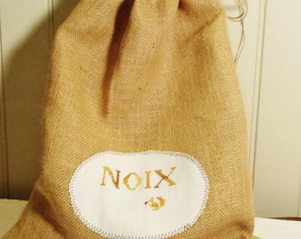 Decorative nut bag in natural burlap with applied cross stitch