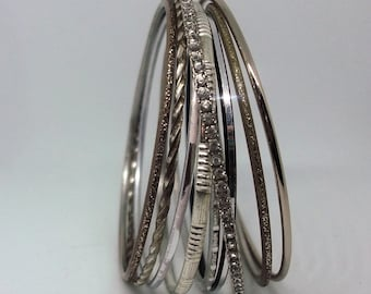 A lovely set of 9 bangles in silver and gold tones with a diamante bangle. 1980s era.