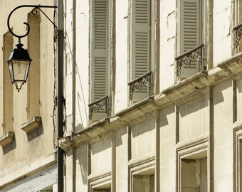 French town houses with white shutters and antique iron lamp, classic street scene, France.