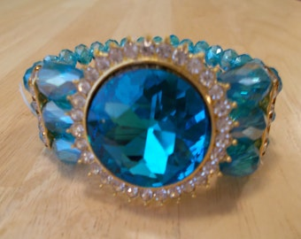 Reduced 3 Row Blue Crystal Stretch Cuff Bracelet with a Gold Tone Frame and Clear Rhinestones
