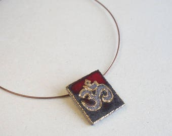 Red pendant Om or Aum lava and gold enamelled Auvergne volcano lava.