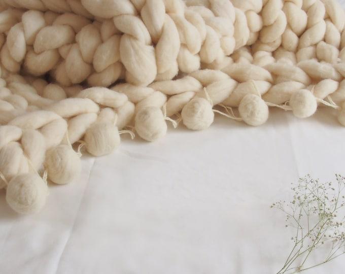 Manta XXL merina Blanca con pompones redondos de lana. Pura lana virgen de origen ecológico.