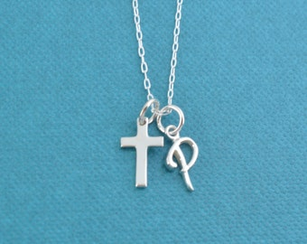 "Little girl's cross necklace in sterling silver on a 14"" sterling silver cable chain and personalized with a sterling silver initial."
