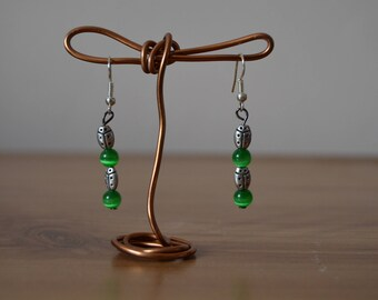 Long green earrings with silver hook clasp and metal ladybugs