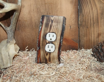 charred wooden outlet cover