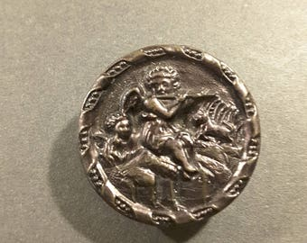 Vintage metal button of cherub playing a flute.