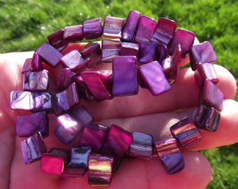 4 PURPLE SHELL BEADS.