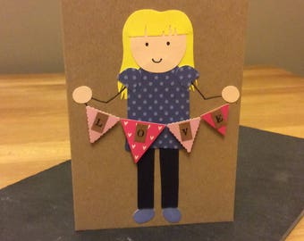 Unique, hand crafted Valentines Day card with lady holding pink love bunting.
