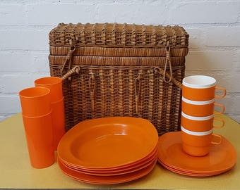 Vintage wicker picnic basket with orange picnic set
