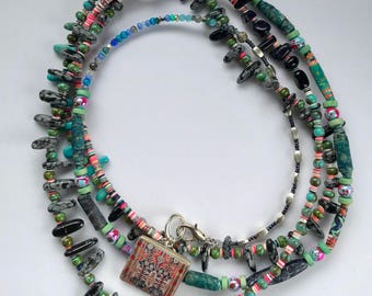 Long multi-strand necklace with tapestry-themed center