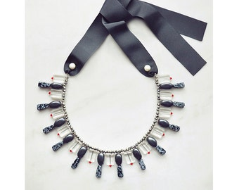 CSC012 - Statement ribbon necklace with gray hematite and snowflake obsidian stones, white pearls and red, silver and clear crystals.