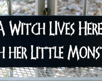 A witch lives here with her little monsters wood sign