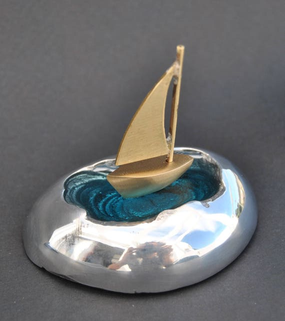 Decoration item, handmade. Aluminum sea stone and brass figures. The color inside the stone is made of glass.