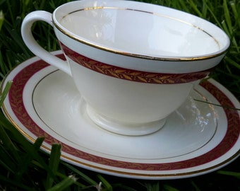 Teacup and saucer by Edwin M Knowles, vintage 1942. White with red and goldleaf bands. Excellent vintage condition with few signs of use.