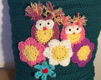 Cushion hand knitted in turquoise with two crochet baby owls and flowers