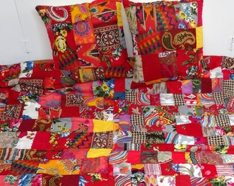 Above bed, blanket, wall hanging in red and multicolored cotton patchwork with 2 matching pillows