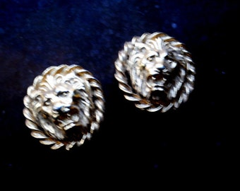 Exotic vintage 80s , gold tone metal , round clip on earrings with a raised lion's face.