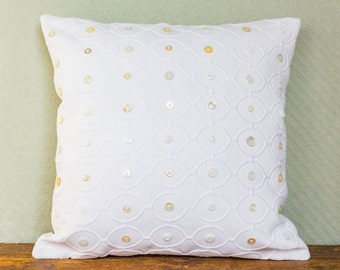 White pillow with assorted white buttons