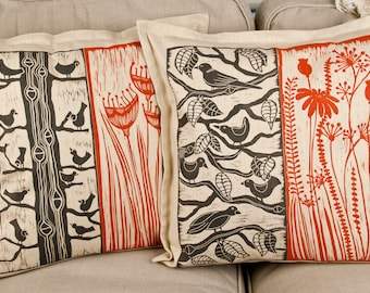 handprinted cushion covers in red and black on beige with my own linocuts on linen fabric, birds, plants, flowers,
