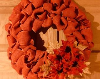 12 in orange burlap wreath with flower accents