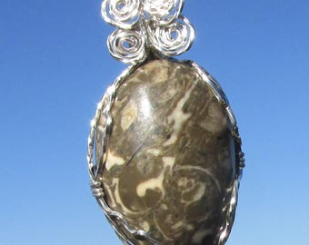 Polished beach rock,   wire wrapped in Argentium Silver wire