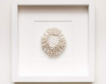 porcelain ceramic sculptural wall art inspired by sea life, framed but without glass