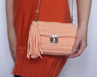 A fancy crochet handbag's cotton-lined with a buckle, has a removable chain based on rings with a tussle.