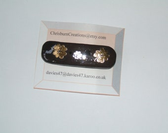 child's black hair barrette with gold and silver flowers
