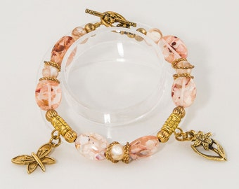 Pink mother of pearl encased in resin  'Flashes of Light' bracelet with charms