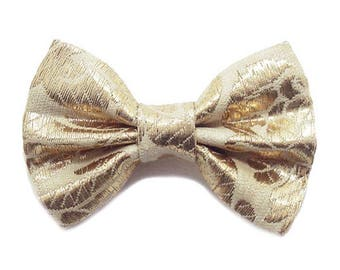 Bow tie brooch, fabric, gold.