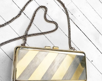 Small gold and silver striped metal hard shell evening bag.