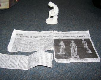 Unglazed white porcelain statuette-boy taking splinter out of his foot 1800's