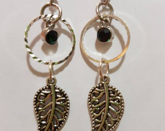 A silver drop earring with green gem and silver leaf