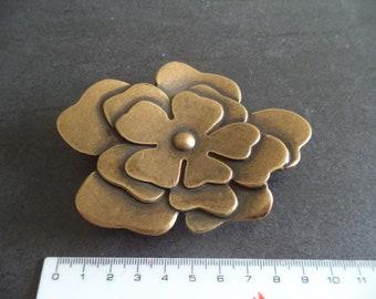 bronze colored metal belt buckle in flower shape