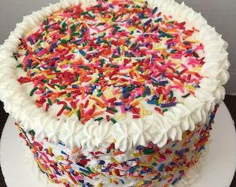 Rainbow sprinkles fake cake.Faux white cakes.