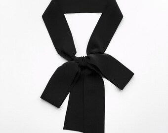 """This black bow tie scarf is 60"""" x 2"""" with square ends in pure silk. Skinny scarves are versatile as a sash, choker tie or headscarf."""