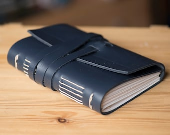A6 Blue Leather bound Journal/sketchbook  with leather strap to close it.